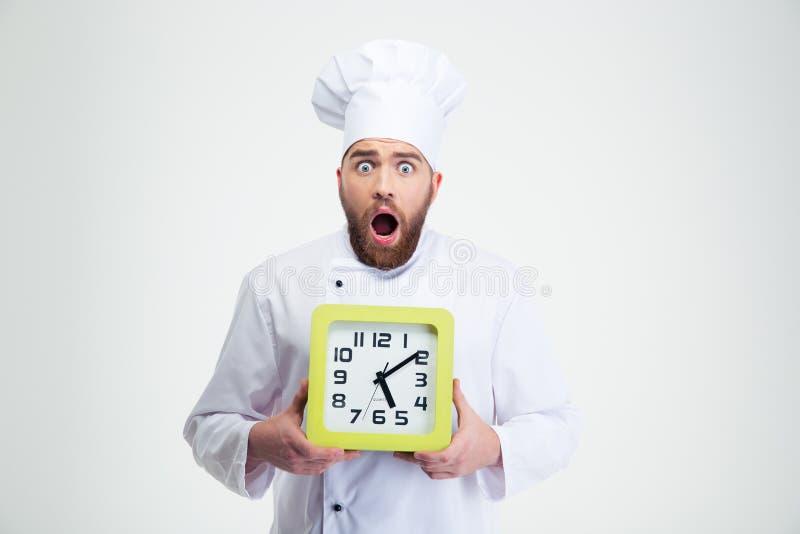 Cuisinier masculin choqué de chef tenant l'horloge murale photos libres de droits