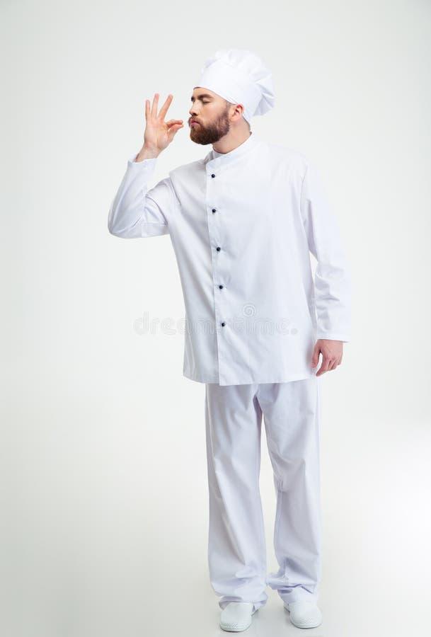 Cuisinier masculin de chef faisant le geste savoureux par les doigts de baiser images stock