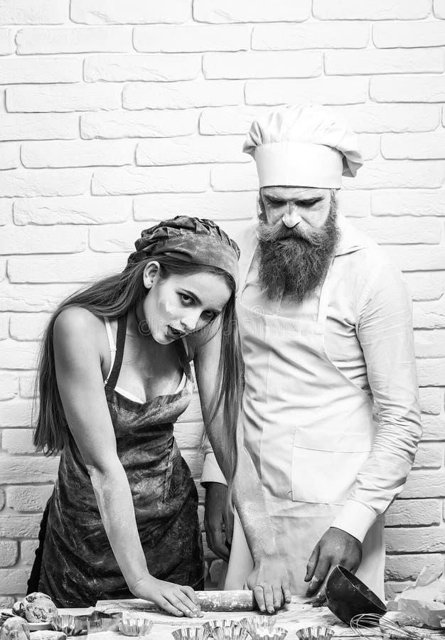 Cuisinier ou boulanger, avec de la farine sur le visage, la barbe, la moustache et la jolie pâte de fille ou belle de femme de pe images stock