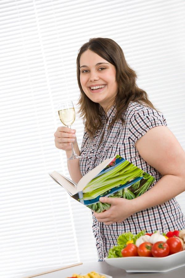 Cuisinier - plus le livre de cuisine heureux de fixation de femme de taille photographie stock
