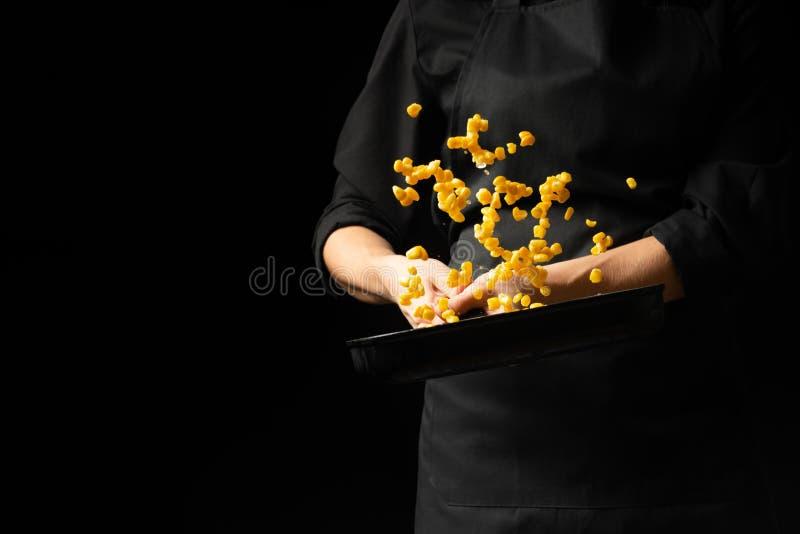 Cuisinier professionnel Le chef prépare un plat avec du maïs dans une casserole Sur un fond noir menu, livre de recette, nourritu photographie stock libre de droits