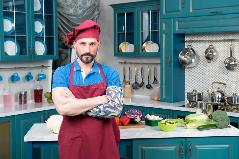 Cuisinier sérieux barbu avec la main tatouée Type dans le tablier rouge à la cuisine image stock
