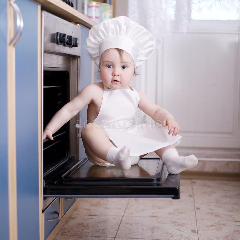 Cuisiniers de chef de bébé dans la nourriture de four image stock