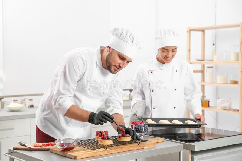 Cuisiniers pâtissiers préparant des desserts à table photographie stock libre de droits