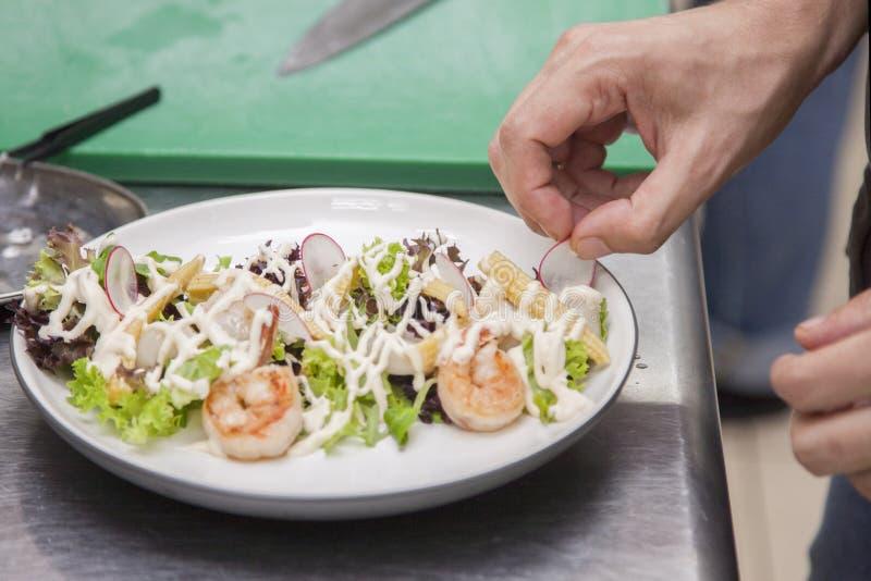 Cuisiniers préparant une salade des fruits de mer image libre de droits