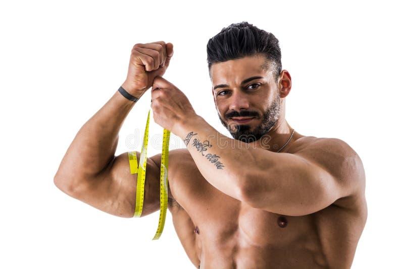 Cuisse de mesure d'homme musculaire de bodybuilder avec le ruban métrique image libre de droits