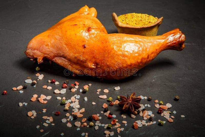 Cuisse fumée de poulet avec des épices et moutarde dans le grain photographie stock libre de droits