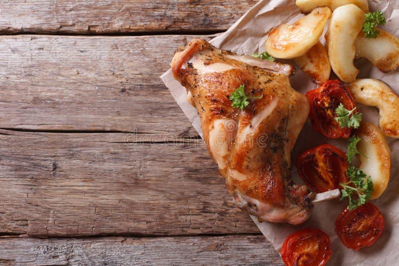 Cuisse savoureuse de rôti de lapin avec la vue supérieure de pommes et de tomates photos stock