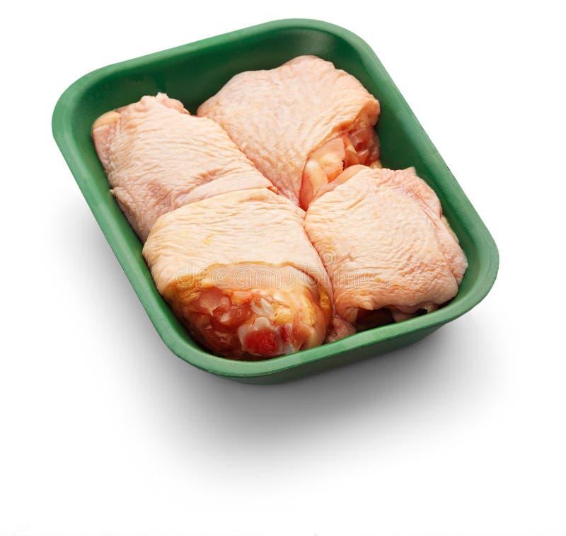 Cuisses crues de poulet dans un plateau vert au-dessus du fond blanc photos stock