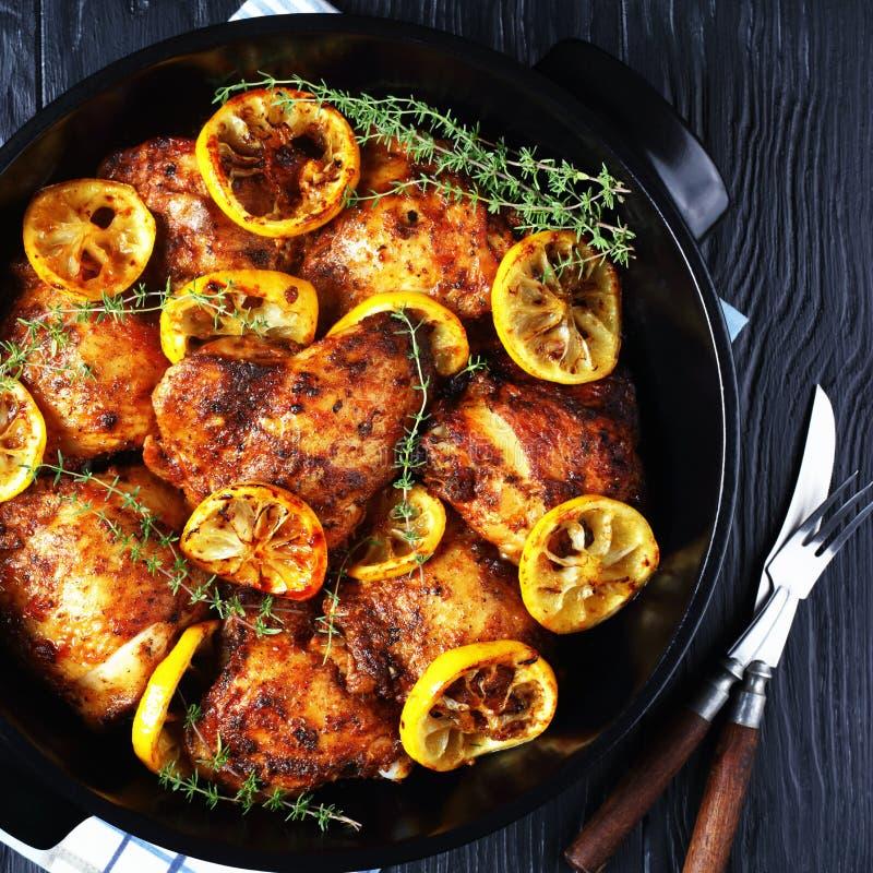 Cuisses de poulet avec tranches de citron dans une poêle photographie stock libre de droits