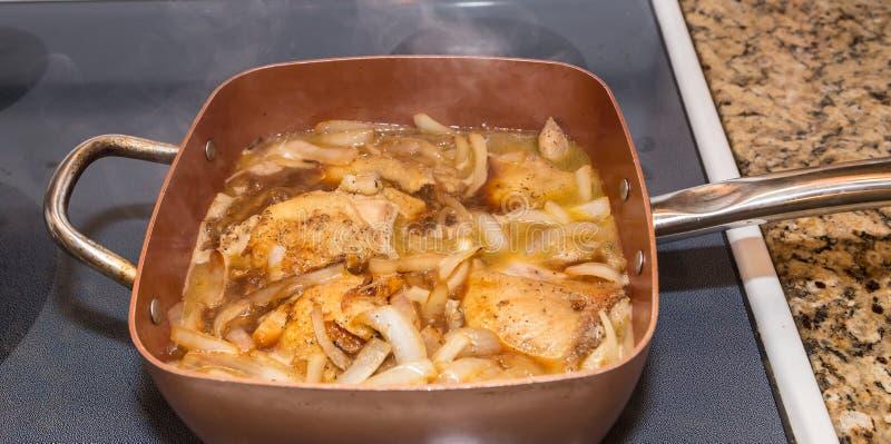 Cuisses de poulet et oignons sautés arrosant en Pino Grigio photos stock