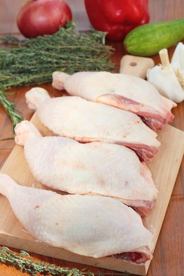 Cuisses de poulet pour faire cuire une cocotte en terre photographie stock