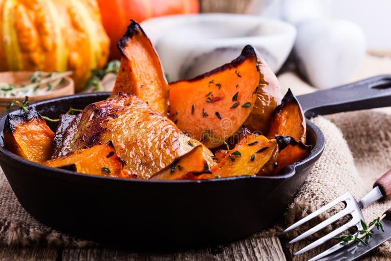 Cuisses de poulet rôti avec la courge de butternut et l'herbe de thym photographie stock libre de droits