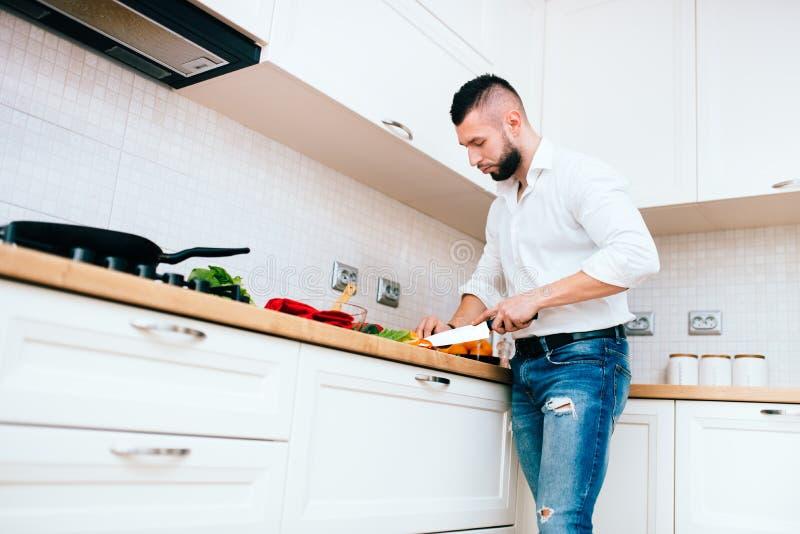 Cuisson d'homme Coordonnées de cuisinier moderne avec le plat de couteau et de cuisine image stock