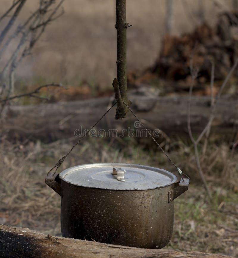 Cuisson dans le vieux chaudron de suie sur le feu de camp image libre de droits