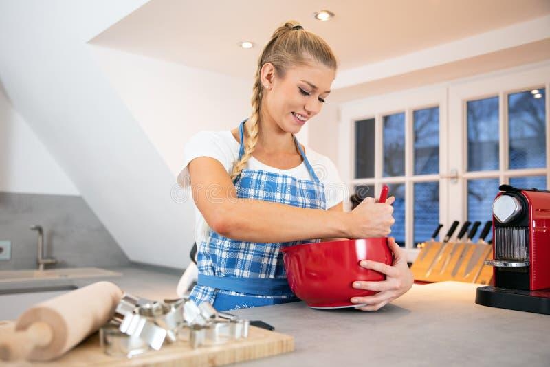 Cuisson de femme dans Noël de cuisine images stock