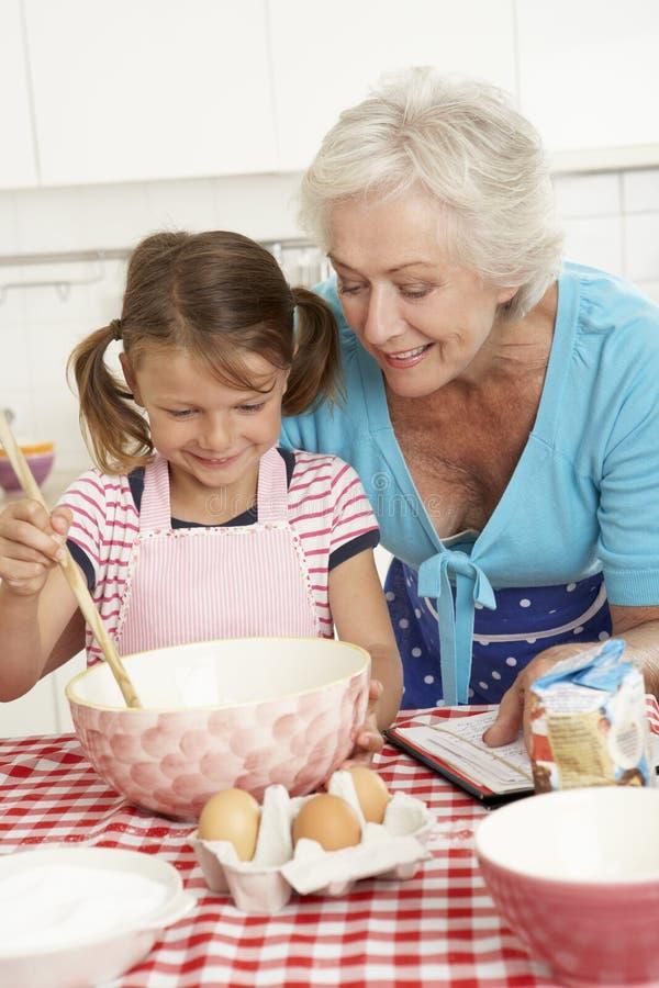 cuisson de grand m re et de petite fille dans la cuisine photo stock image 55897510. Black Bedroom Furniture Sets. Home Design Ideas