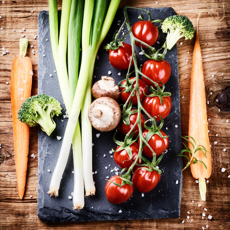 Cuisson de l'arrangement avec les légumes organiques frais sur le vieux backgr en bois photo libre de droits