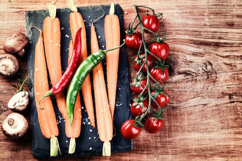 Cuisson de l'arrangement avec les légumes organiques frais sur le vieux backgr en bois image libre de droits