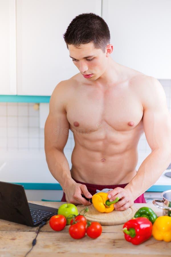 Cuisson de l'Internet sain r de légumes de bodybuilder de jeune homme de repas photographie stock