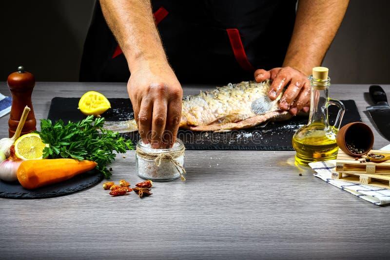 Cuisson de la carpe, du citron, des herbes et des épices de poissons par les mains de chef, étapes sur la cuisine noire de fond P photos stock