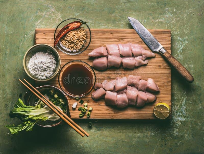 Cuisson de la préparation des morceaux de poulet de teriyaki avec des ingrédients : blanc de poulet d'intestin, arachide et oigno images stock
