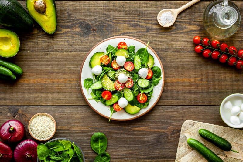 Cuisson de la salade fraîche Légumes, verts, épices, plat de salade sur la vue de bureau de cuisine en bois foncée image libre de droits