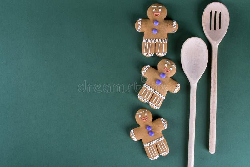 Cuisson de Noël et de vacances Biscuits d'hommes de gingembre avec le décor sur le vert photo libre de droits