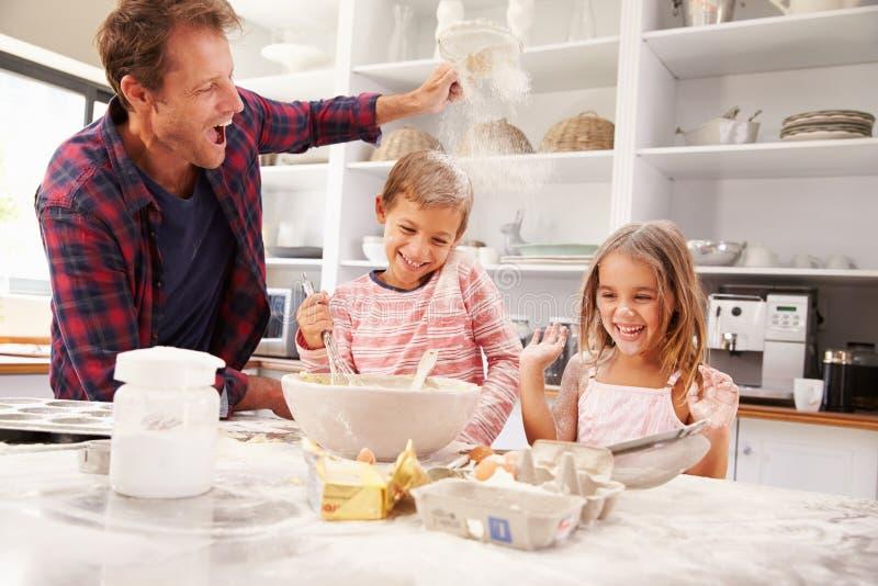 Cuisson de père avec des enfants photographie stock libre de droits