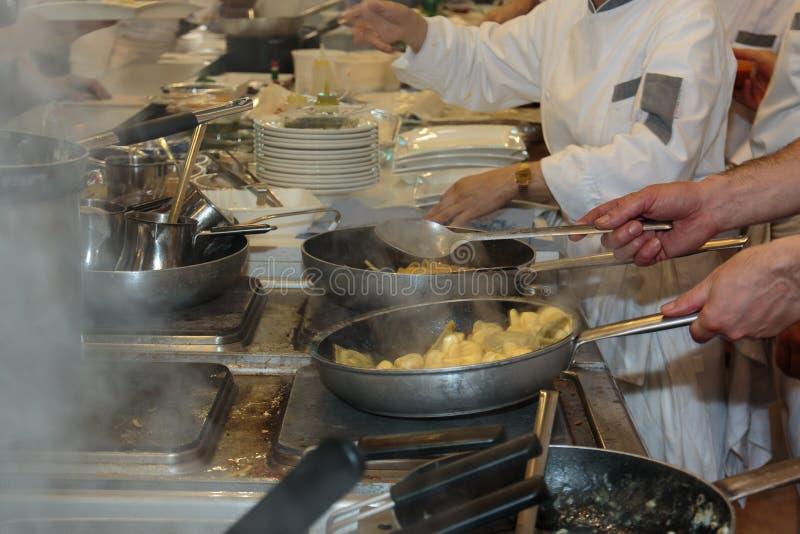 Cuisson de Restaurant& intérieur x27 ; cuisine, casseroles et chef de s avec l'uniforme photos libres de droits