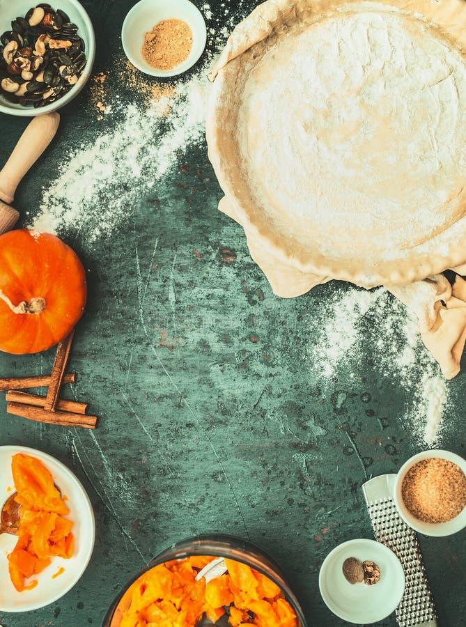 Cuisson de tarte de potiron : pâte en forme, remplissage et ingrédients de support sur le fond rustique foncé, vue supérieure photos stock
