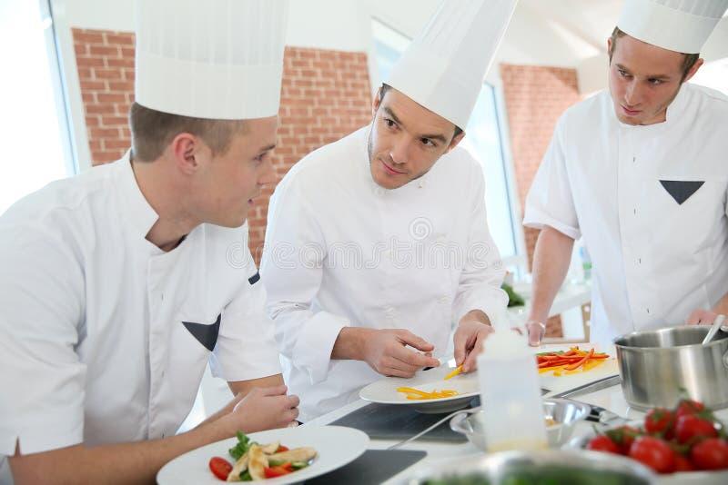 Cuisson des apprentis avec le chef préparant des plats photo libre de droits