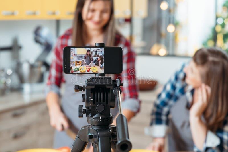 Cuisson des femmes du blog deux tirant le smartphone visuel images libres de droits