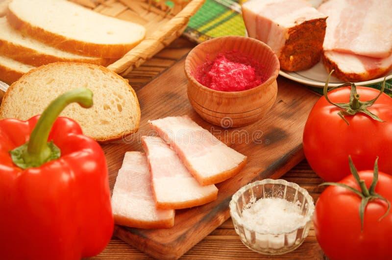 Cuisson des ingrédients pour des sandwichs avec le lard et les tomates de porc de bajoue photographie stock