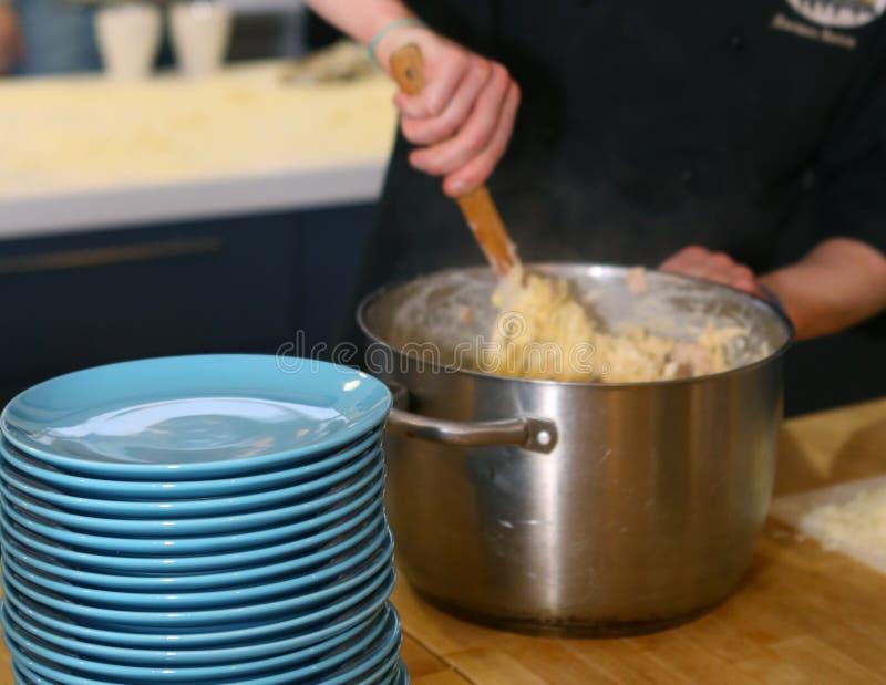 Cuisson des pâtes dans le grand stylo de fer pour le dîner de approvisionnement photographie stock libre de droits