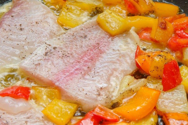 Cuisson des poissons et des poivrons photographie stock