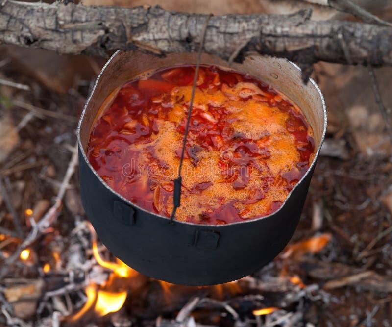 Cuisson du borscht (soupe traditionnelle ukrainienne) sur le feu de camp image libre de droits