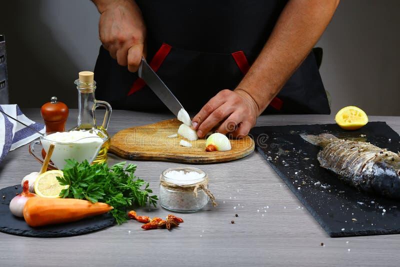 Cuisson du poisson frais pour la cuisson par des mains de chef sur le fond en bois de table, cuisinier coupant en tranches l'oign image libre de droits