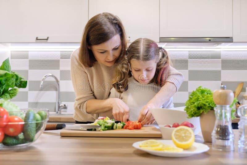 Cuisson du repas ? la maison sain par la famille La m?re et la fille ont coup? des l?gumes ? la maison dans la cuisine pour la sa image stock