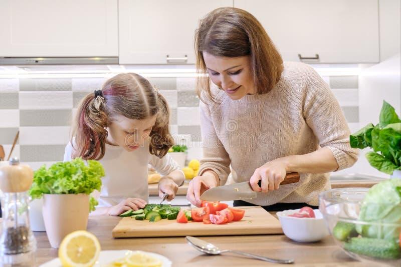 Cuisson du repas ? la maison sain par la famille La m?re et la fille ont coup? des l?gumes ? la maison dans la cuisine pour la sa images stock