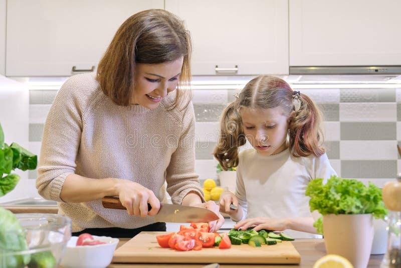 Cuisson du repas ? la maison sain par la famille La m?re et la fille ont coup? des l?gumes ? la maison dans la cuisine pour la sa image libre de droits