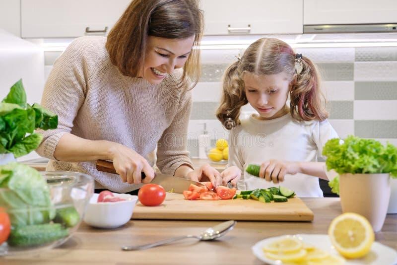 Cuisson du repas ? la maison sain par la famille La m?re et la fille ont coup? des l?gumes ? la maison dans la cuisine pour la sa photographie stock libre de droits