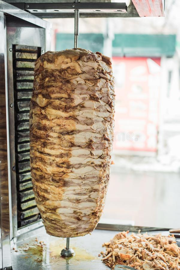 Cuisson du shawarma et de la ciabatta dans un café Un homme en viande de coupes de gants jetables sur une brochette images stock