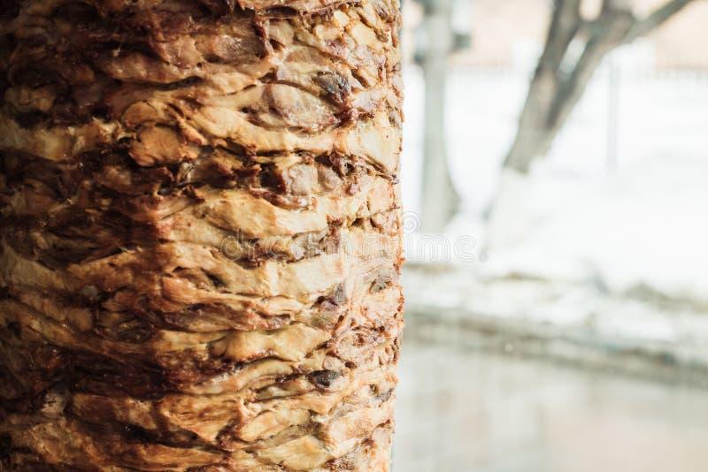 Cuisson du shawarma et de la ciabatta dans un café Un homme en viande de coupes de gants jetables sur une brochette images libres de droits