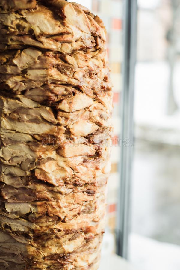 Cuisson du shawarma et de la ciabatta dans un café Un homme en viande de coupes de gants jetables sur une brochette photos stock