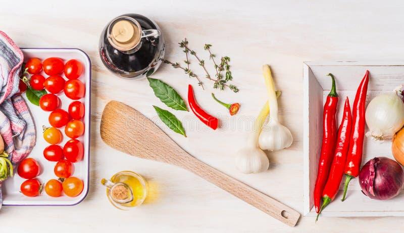 Cuisson saine avec de diverses épices fraîches : huile d'olive, piment, oignon, ail et feuilles de baie sur le fond en bois blanc images stock