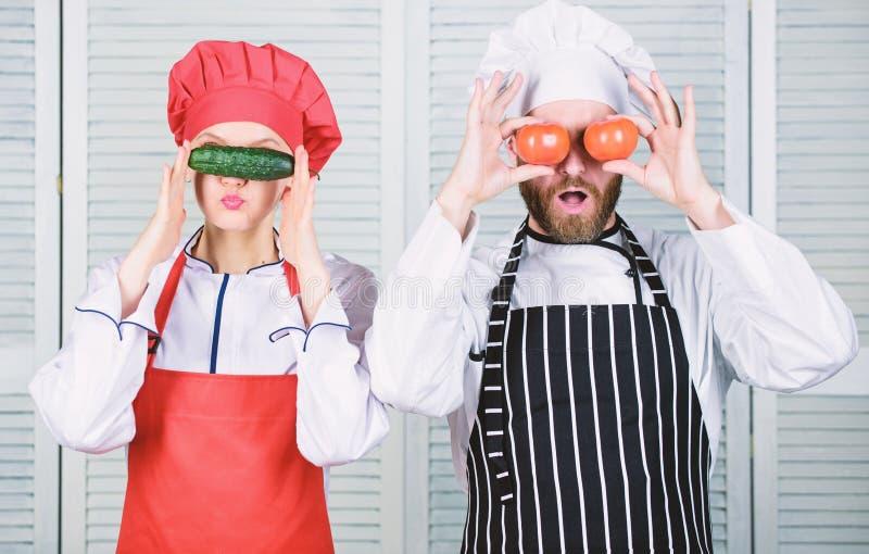 Cuisson saine Couplez des cuisiniers ayant l'amusement avec la nourriture saine naturelle Chef et aide-cuisinier jouant avec des  photographie stock libre de droits