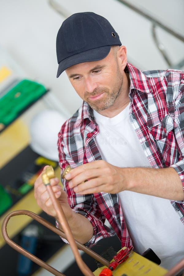 Cuivre et garnitures de soudure de plombier avec le chalumeau image stock