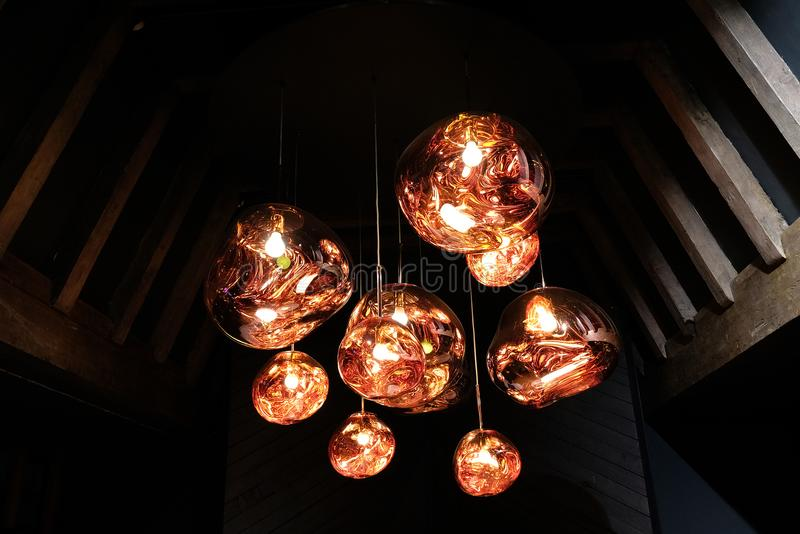 Cuivrez le montage léger pendant en verre coloré accrochant dans le grenier avec les faisceaux en bois images stock