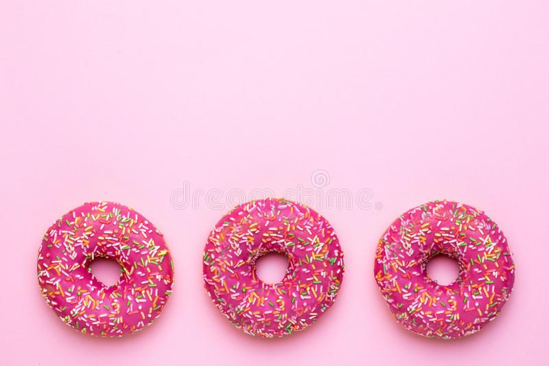 Cukierków różowi donuts z stubarwnym kropią na różowym tła mieszkaniu nieatutowym obrazy royalty free